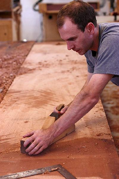 Austin Weeks planing mahogany planks with his great, great, great grandfather's wooden plane