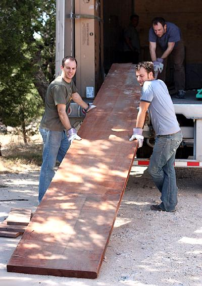 Austin, Will, and Aaron unloading large mahogany plank