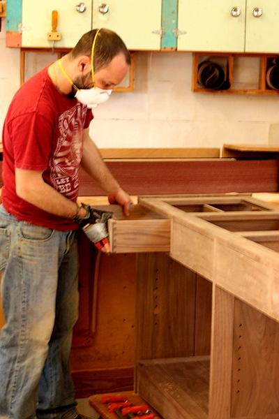 Aaron is fitting a drawer of a walnut buffet.