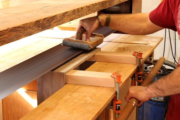 Detail of sanding a drawer to fit with a stroke sander